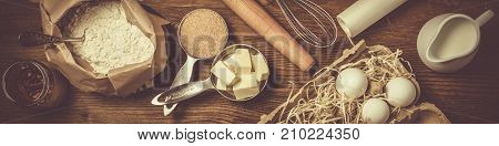 Baking ingredients in measuring cups, rustic wood background