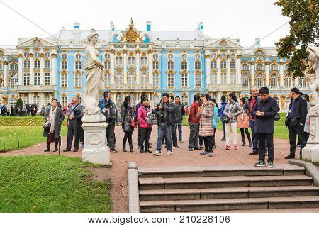 Pushkin, Russia - 5 October, A group of tourists at the palace, 5 October, 2017. A rainy day in an autumn park.