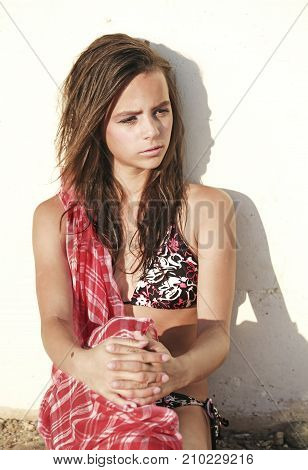 Intensely tanned girl on white wall background. Summer vacation