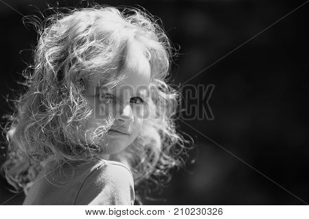 Outdoor portrait of a cute little girl with curly hears, looking back over her shoulder. black and white.