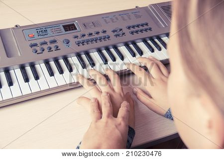 Woman teaching little girl to play the synthesizer