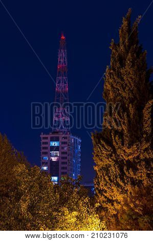 Apartment building and base station seen behind trees on the background of clear sky at dusk Sochi Russia