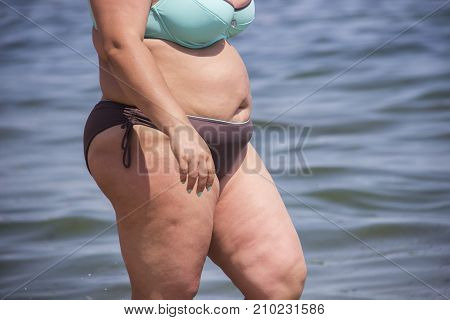 Overweight young woman in swimsuit near the sea looking at the water enjoys the hot sun in his summer holiday