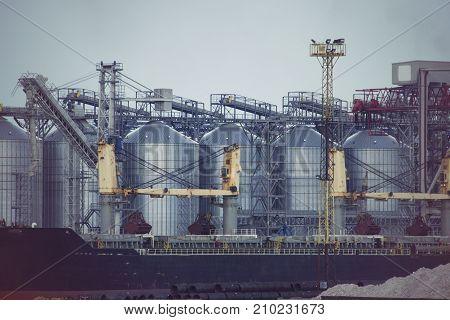 Port grain elevator. Industrial sea trading port bulk cargo zone grain terminal.