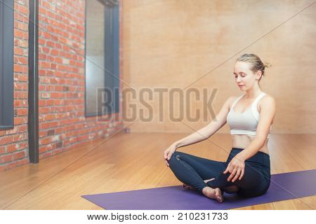 Attractive young woman sitting in lotus position in a yoga studio