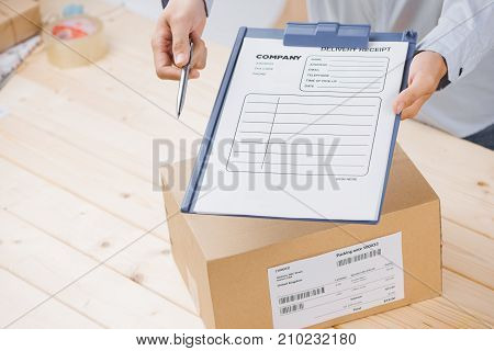 Delivery Man Presenting Receiving Form In Post Office