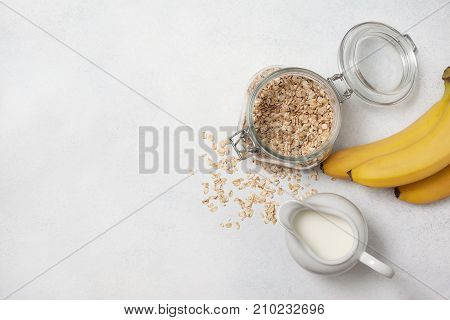 Ingredients for breakfast: milk oatmeal bananas on a light background. view from above copy space
