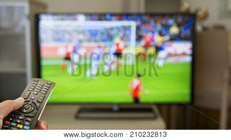 Watching soccer at home on TV and remote control