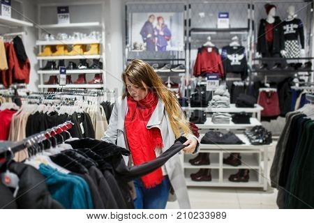 Shopping, fashion, sale, , style and people concept - young woman in grey coat and red scarf choosing black jacket in clothing store.