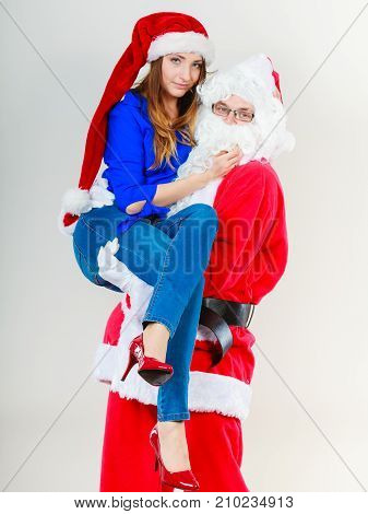 Christmas holiday concept. Man wearing Santa Claus costume holding woman in christmassy hat.