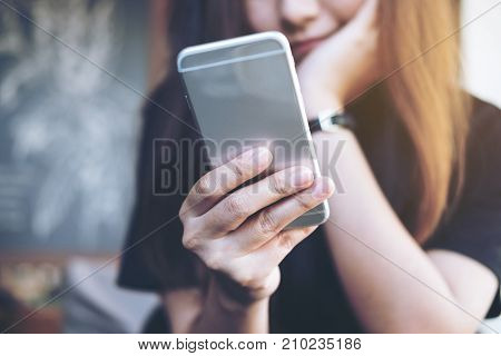 Closeup image of a beautiful Asian woman holding and using at smart phone sitting in modern cafe