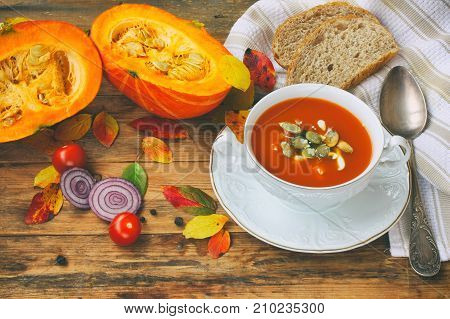 pumpkin soup puree in white bowl on wooden table onion leaves rustic style autumn composition