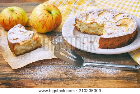 homemade apple pie on plate dusted with icing sugar piece of cake on paper on wooden table rustic style