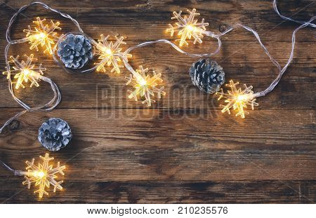 christmas new year greeting card fir cones garland light snowflakes border on an old wooden table space for text