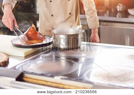 Fresh boiled shank of lamb. Male chef putting on large piece of boiled lamb shank on white kitchen paper.