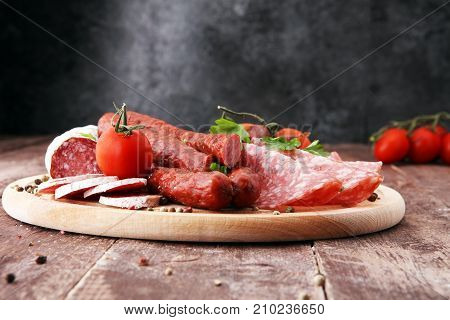 Food tray with delicious salami pieces of sliced ham sausage tomatoes salad and vegetable - Meat platter with selection - Cutting sausage and cured meat