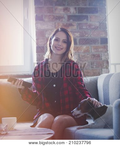 Young Woman With Cup Of Tea Or Coffee Sitting At Sofa