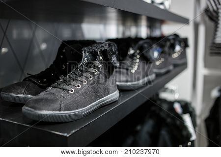 Shoes - black sneakers on the shelf in the store.
