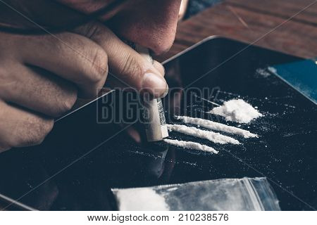 Drug addict man sniffing cocaine on tablet pc with rolled banknote, close up. Drug abuse concept
