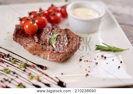 Steak ribeye with sauce from madagascar pepper.Tasty dish of restaurant with european cuisine. Appetizing food on white porcelain plate.