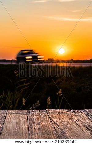 Empty Rustic Wood Table Top With Motion Car At Sunset Background. Can Montage Or Display Your Produc