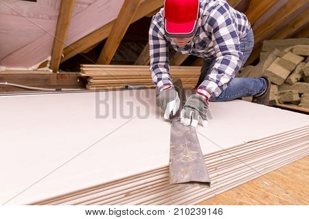worker cutting plasterboard with construction knife. Attic renovation