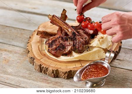 Chef served roasted calf ribs with cherry. Delicious grilled calf ribs with sauce and vegetables. Appetizing dinner on wooden stand.