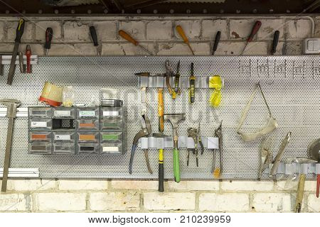 Old tools hanging on wall in metalwork workshop Tool shelf against a wall