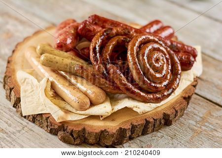 Grilled appetizing sausages on platter. Octoberfest traditional food. Tasty grilled sausages, german food. Delicious fried sausages on board.