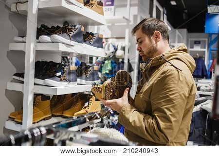Bearded man hipster in beige jacket choosing yellow winter boots in store - shopping, fashion, sale, , style and people concept.