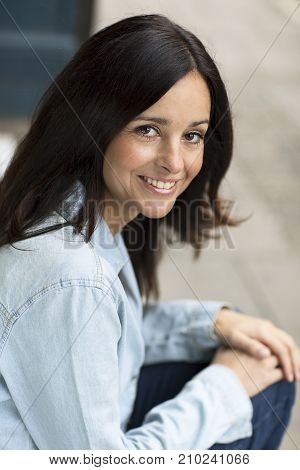 a happy young woman sitting on her doorstep