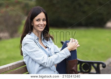 a happy woman sitting in the park