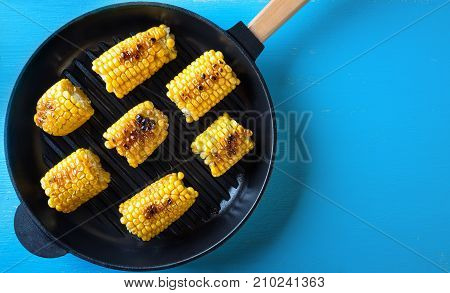 Hot baked corn in a frying pan. Blue background. View from above. The concept of healthy natural food.