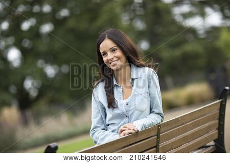happy young womna sitting on a bench in the park