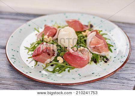 Prosciutto and arugula salad with burrata. Burrata mozzarella salad accompanied by prosciutto and arugula. European food and cuisine.