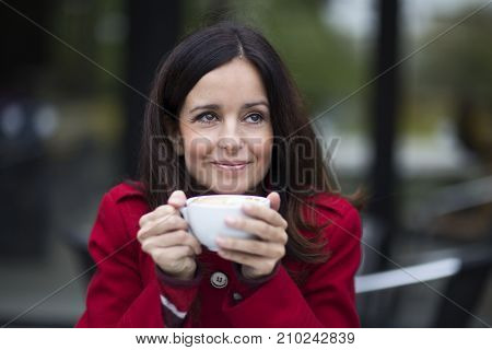 a young woman enjoying a coffee and thinking