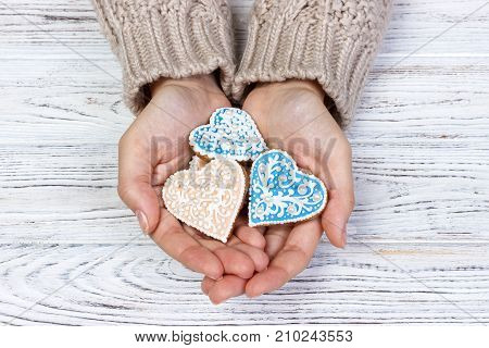 Heart-shaped cookie in woman's hands. holiday cookies