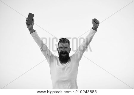 One handsome young bearded emotional business man in white sweater holding cell phone outdoor on light sky natural background horizontal picture