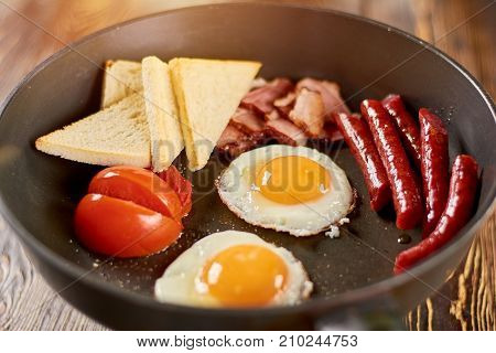Hot english breakfast in skillet. Fried eggs with yolks, baked sausages and ham, toasts and tomatoes. Fresh english breakfast.