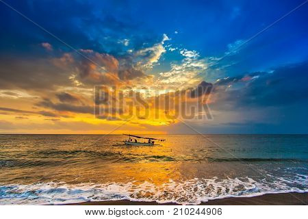A fishing boat goes to the ocean in the evening. Bright colorful orange sun hidden in dense blue clouds over the Bali Sea. A white wave pours a foam to the sandy beach. Sunset on the Lombok Indonesia