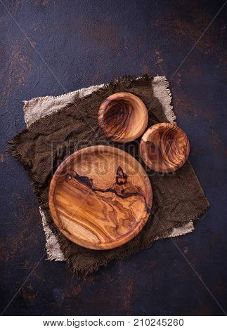 Empty wooden plate and bowls on rusty background. Top view