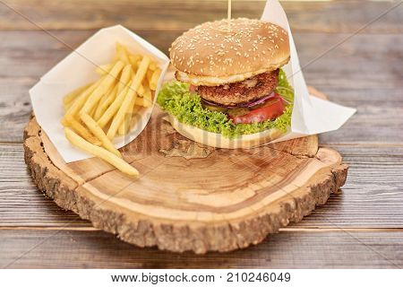 Hamburger with fresh vegetables and meat. Burger with beef, tomato, lettuce, pickled cucumbers. Cheesburger on rustic wooden background.