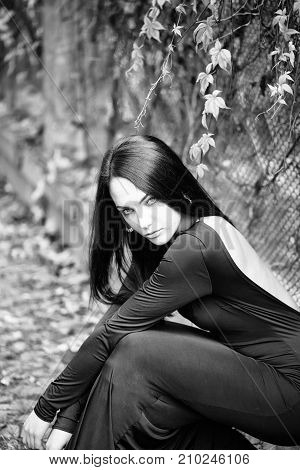 One sexual young attractive brunette woman with long hair sitting in forest near fense with autumn leaves plant in black dress outdoor on natural background vertical picture