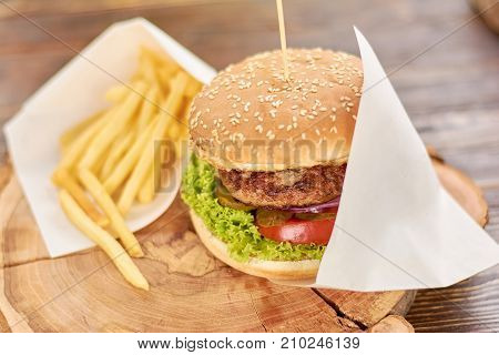 Burger with fried potatoes on wood. Classic american food - burger. Appetizing burger with fresh vegetbles, meat and french fries.