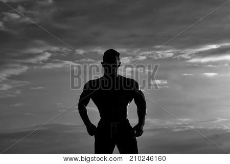 young macho man model athlete silhouette with muscular sexy body and bare chest outdoor on sky background