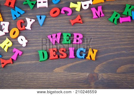 web design. website development and technology background. various colored wooden letters on a dark plate.