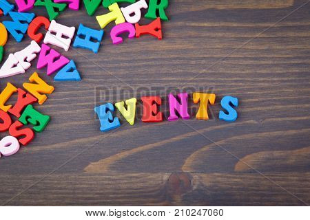 events. arious colored wooden letters on a dark plate.