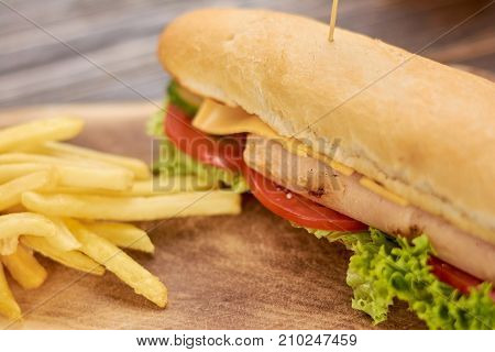 Delicious hot dog and french fries. Appetizing hot dog with lettuce, tomatoes, cucumbers, cheese, chicken sausage on wooden background.