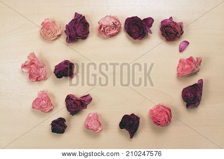 Wilted roses on pastel wooden background, top view. Valentines day background