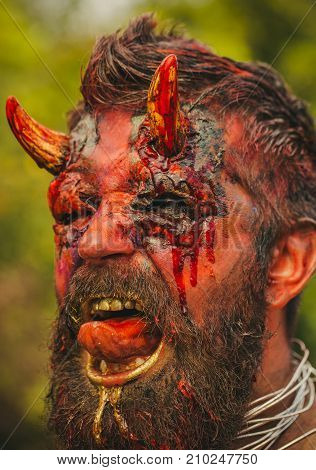 Halloween devil head with bloody horns. Demon man with beard showing tongue. Satan with red blood and wounds on face skin. Dragon creature witcher. Temptation hell evil horror darkness concept.